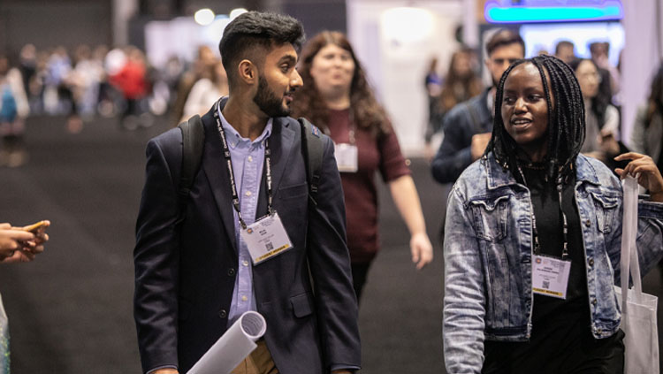 Image of two young adults talking while walking through the poster floor at Neuroscience 2019.