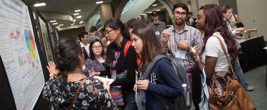 Several people gather at a scientific poster at the SfN annual meeting