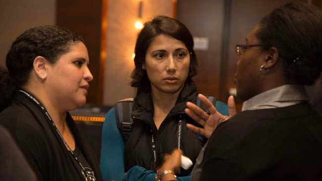 Three female faculty talk at a conference.