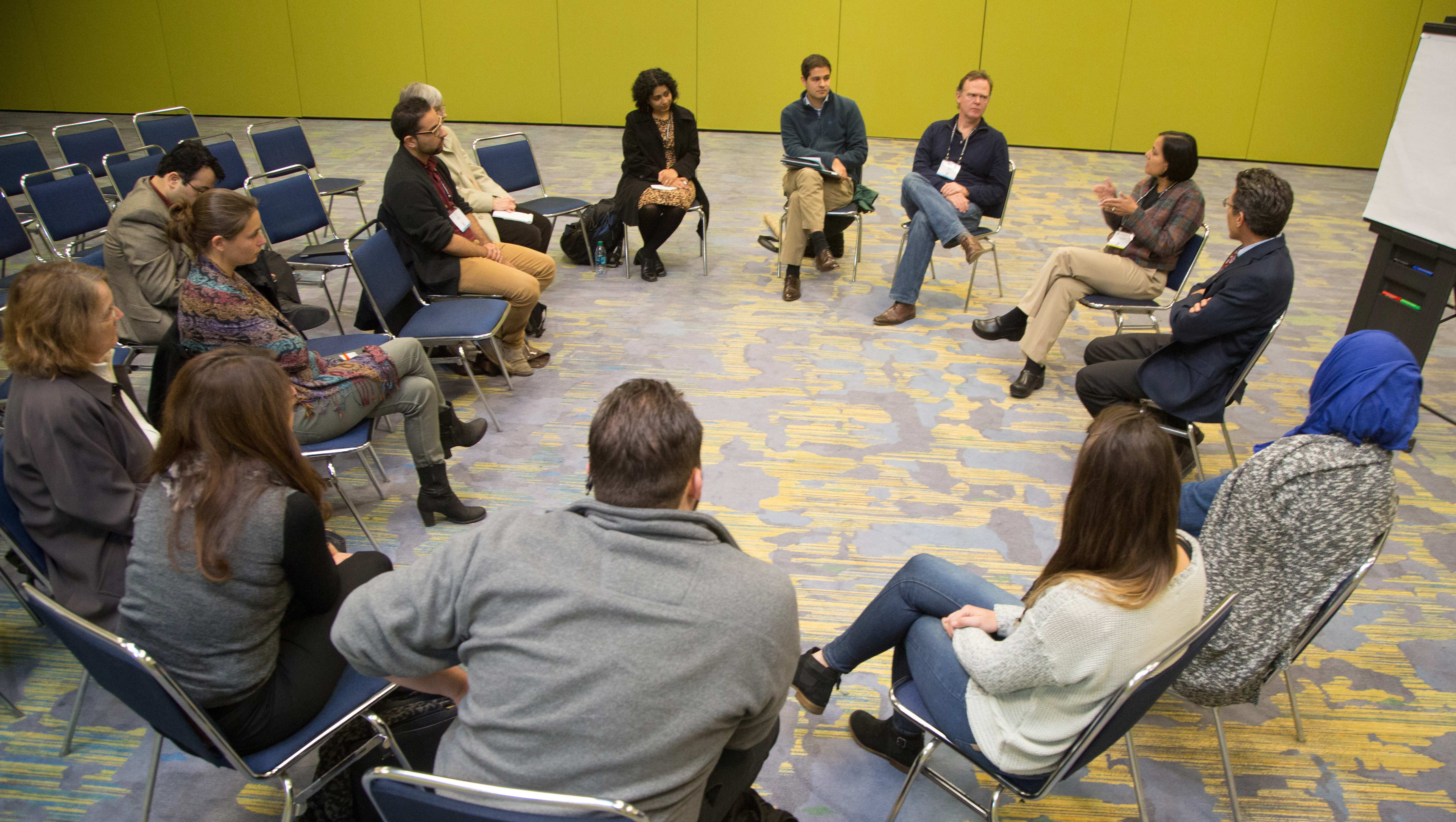 A group of faculty and students sit in a circle and have a discussion.