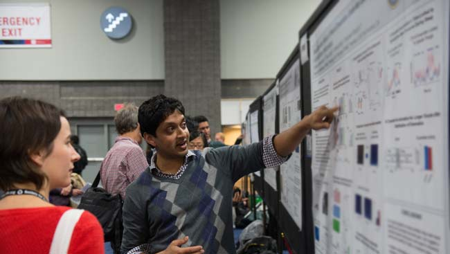 A male neuroscientist shares his science at the SfN annual meeting poster session.