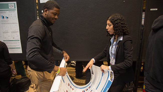 Attendees assisting each other on the poster floor at Neuroscience 2017.