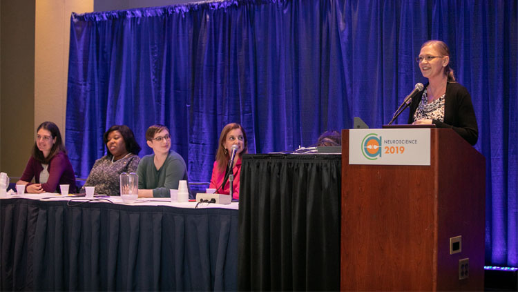 Four women panelists sit listening intently to a speaker.