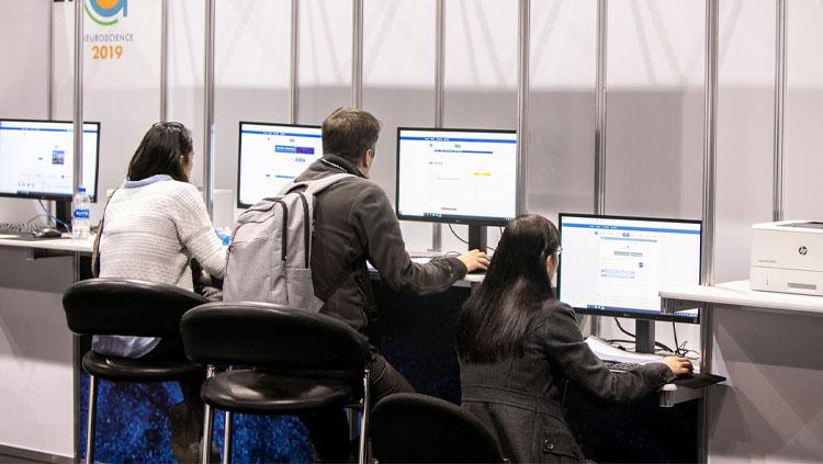 Three young adults look through job postings at the NeuroJobs center at Neuroscience 2019.
