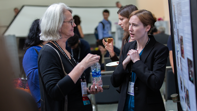 Image of two women discussing a poster at Neuroscience 2018