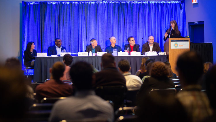 Seven panelists sit at a table discussing social issues at Neuroscience 2019
