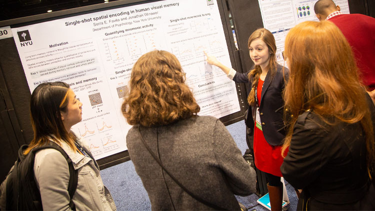 Three people listen as a young woman explains her research poster at Neuroscience 2019.